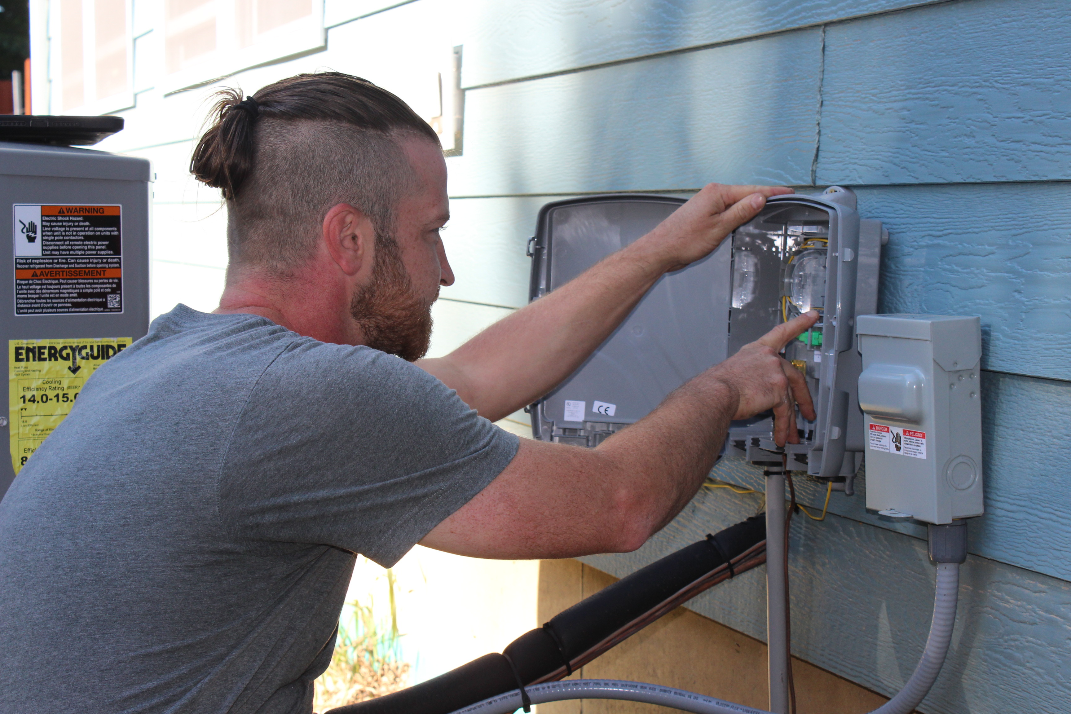 Fiber technician installing hardware to side of house