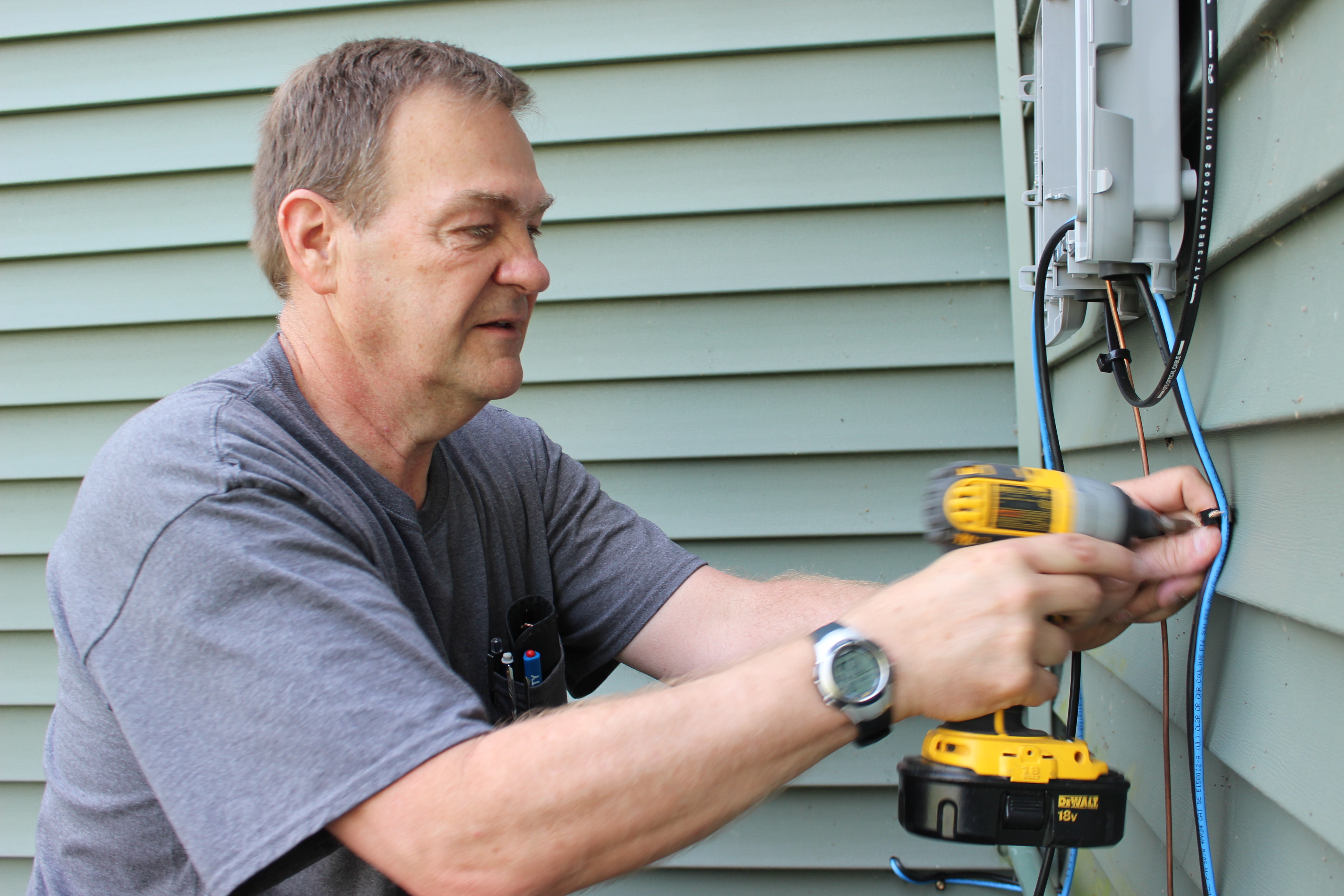 Fiber technician Gary Martin installs outdoor ONT onto a home.